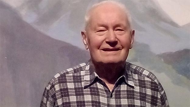 Ein Mann mit kariertem Hemd vor einer gemalten Bergkulisse.