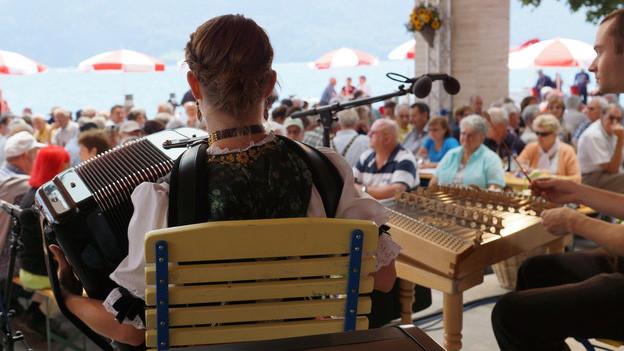 Eine junge Akkordeonistin spielt auf einer Bühne mit Blick auf den Vierwaldstättersee.