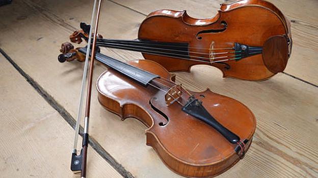Zwei Geigen auf einem Holzboden.