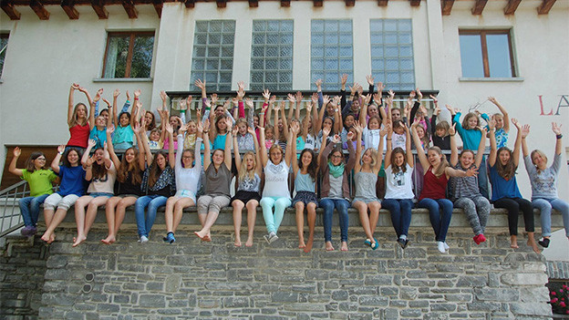 Eine Gruppe Mädchen mit in die Höhe gestreckten Armen singt auf einer Mauer.