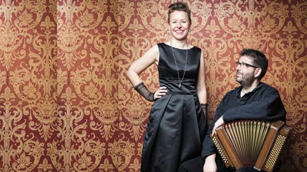 Eine Sängerin im Abendkleid steht neben einem sitzenden Akkordeonspieler.