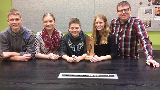 Vier junge Menschen und ein Moderator an einem langen Tisch.