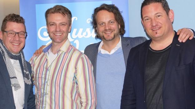 vier Männer vor Musikwelle Logo.