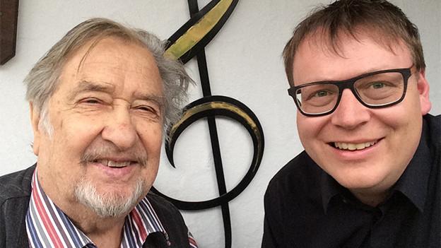 Selfie mit zwei Männern vor einem Hauseingang.