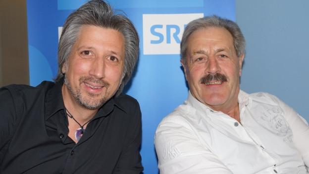 Sepp Silberberger und Moderator Roger De Win vor Musikwelle-Logo.