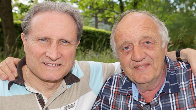 Zwei Männer in einem Garten.