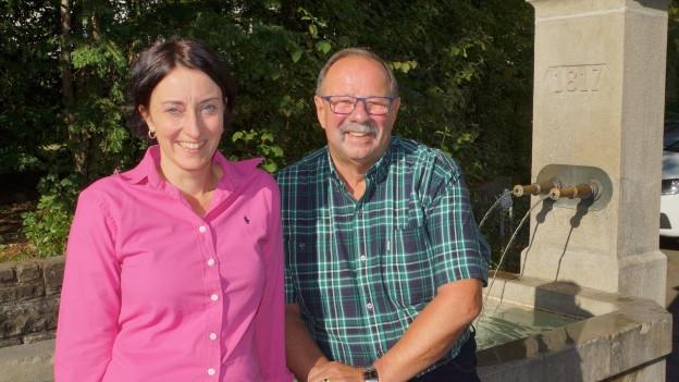 Renate Anderegg und Arno Jehli sitzen auf dem Brunnen.