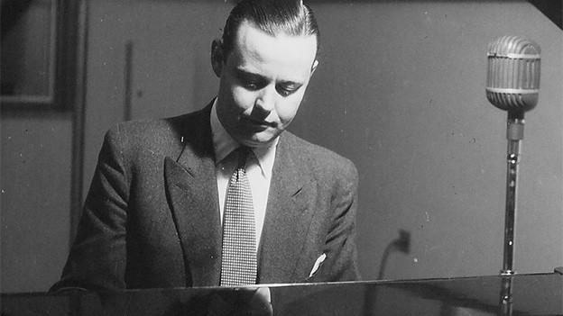 Schwarz-Weiss-Fotografie von einem spielenden Pianisten.