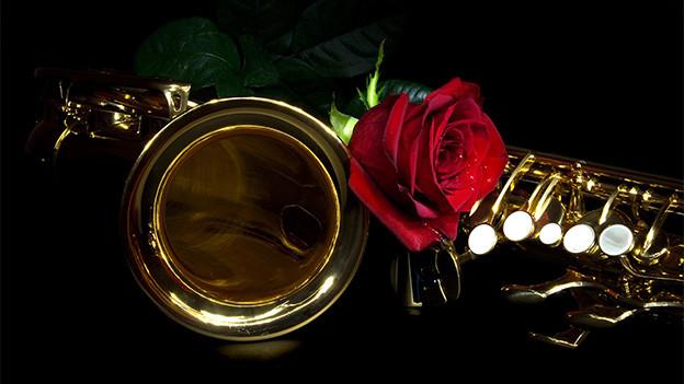 Eine rote Rose liegt neben einem Saxofon.