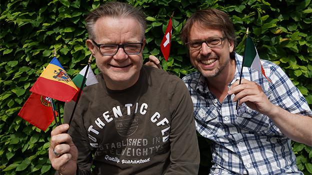 Zwei Männer mit kleinen Landesflaggen.