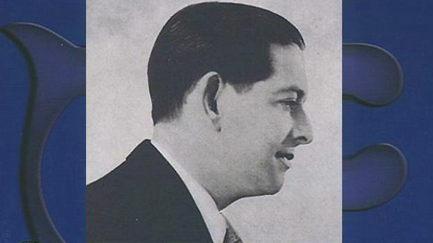 Porträtfoto eines Mannes auf blauem Hintergrund.