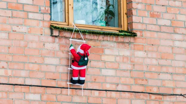 Santa Claus an einer Leiter als Weihnachtsdekoration.