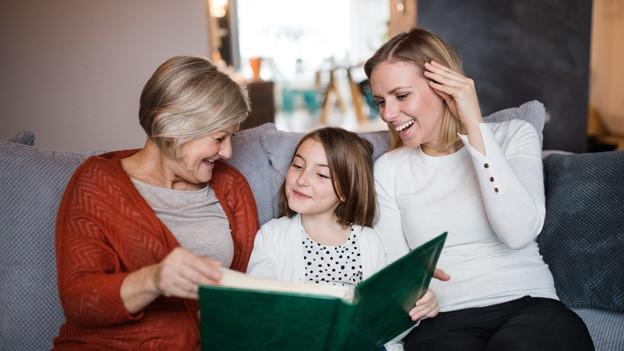 Grossmutter, Enkelkind und Mutter schauen sich ein Fotoalbum an.