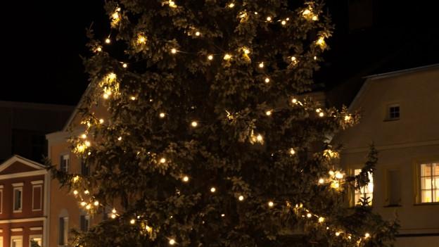 Ein beleuchteter Christbaum der draussen steht.