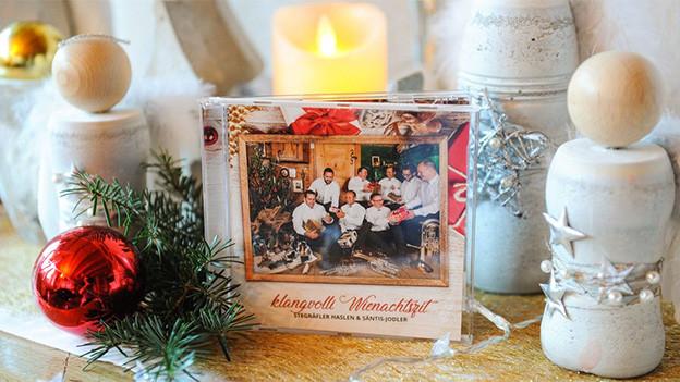 Eine CD umgeben von Weihnachts-Dekoration.