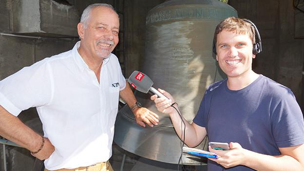 Interviewpartner und Reporter stehen vor einen gusseisernen Glocke.