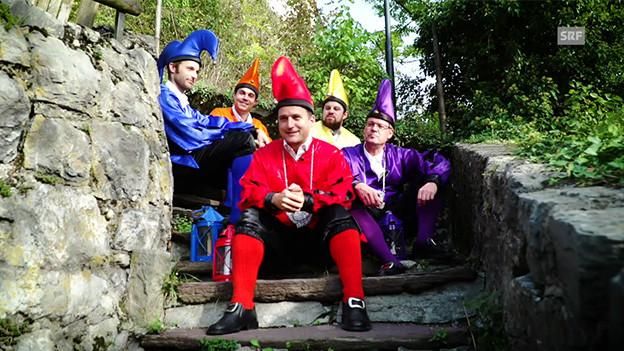Eine Gruppe Männer in farbiger Kleidung sitzt auf einer Treppe.