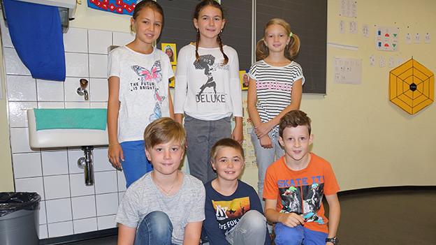 Eine Gruppe von Mädchen und Buben im Schulhaus.