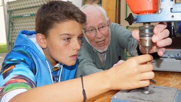 Ein ältere Mann erklärt einem Teenager die Bohrmaschine.