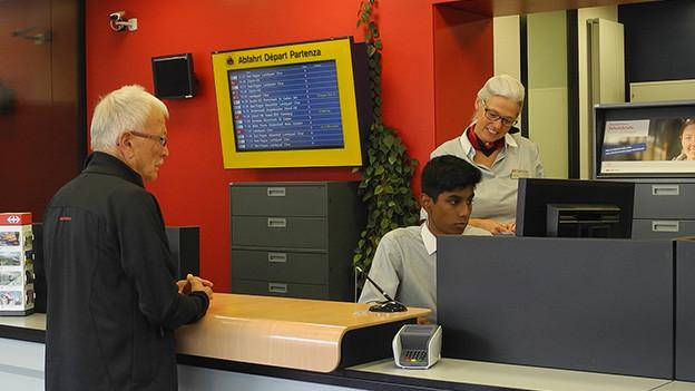 Ein Mann wird am Bahnhofschalter von einem Lehrling beraten.