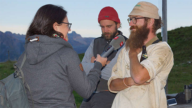 Eine Reporterin interviewt zwei Männer auf einer Alp.