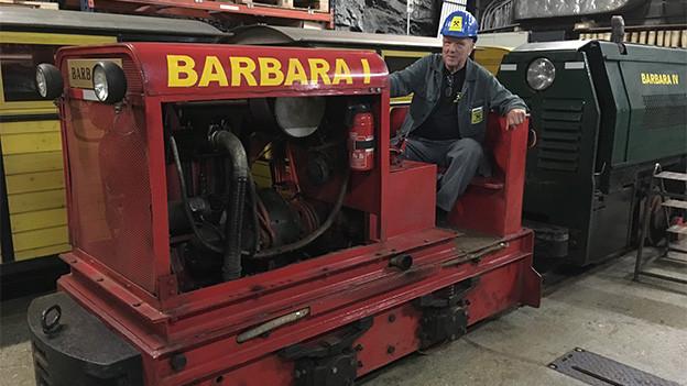 Ein Mann auf einen kleinen Zugskomposition in einem Bergwerk.