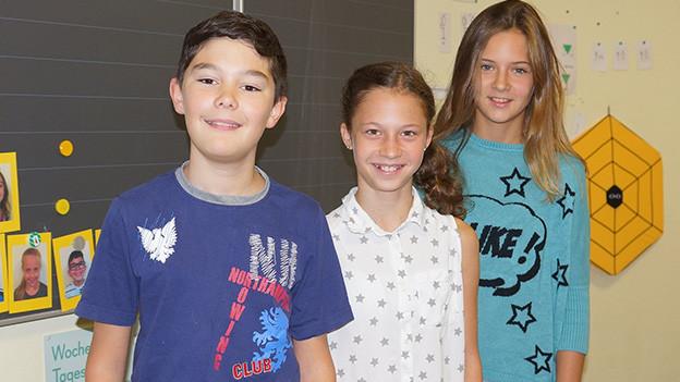 Ein Schüler und zwei Schülerinnen in einem Schulzimmer.