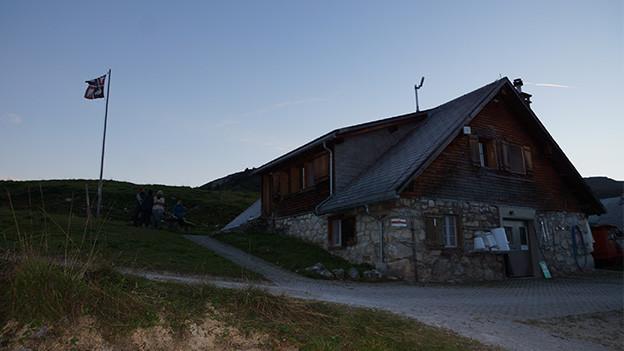 Eine Alphütte in der Abenddämmerung.