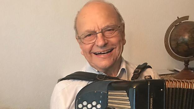 Ein älterer Mann mit Akkordeon in seinem Wohnzimmer.