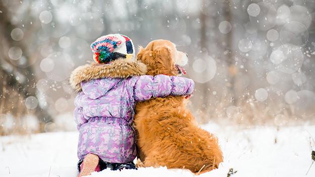 Ein Kind und ein Hund freuen sich über den Schneefall.