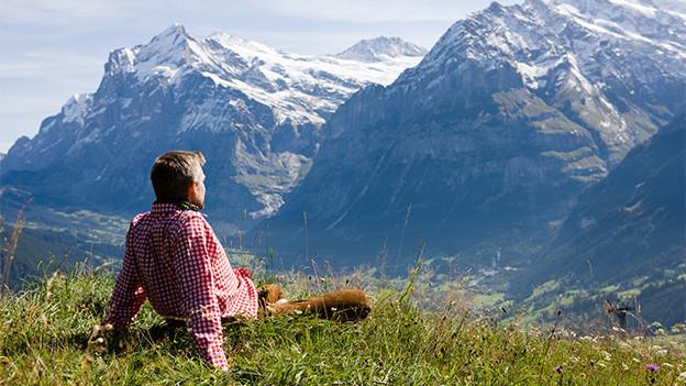 Ein Mann sitzt in einer Wiese mit Blick auf die Berge.