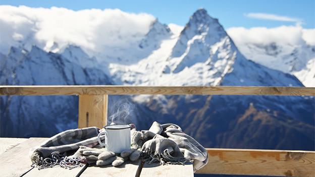 Ein Schal und eine Tasse auf einer Sonnenterrasse in den Bergen.
