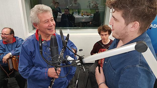 Zwei Männer vor einem Mikrofon im Gespräch.