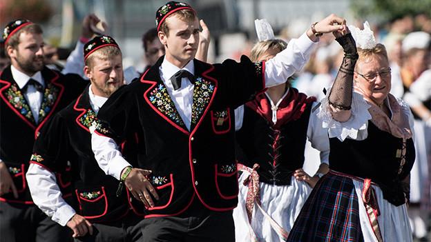 Tanzende Trachtenleute während eines Umzugs.