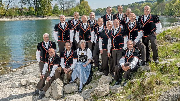 Gruppenbild mit Trachtenfrauen und -männern am Ufer eines Flusses.