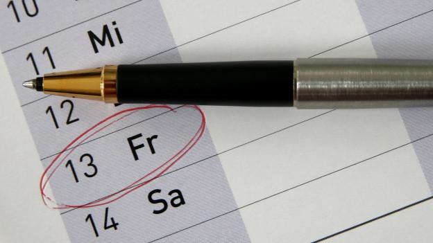 Kalenderblatt mit Kugelschreiber, Freitag der 13. ist rot eingekreist.