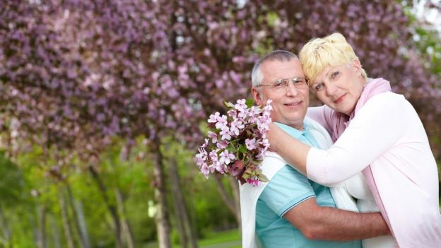 Frau und Mann umarmen sich vor einem blühenden Baum.