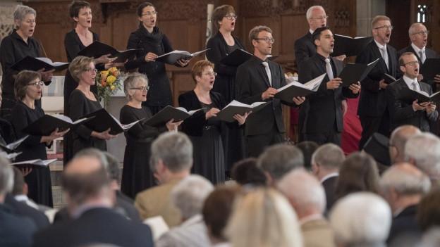 Ein Chor singt in einer Kirche.