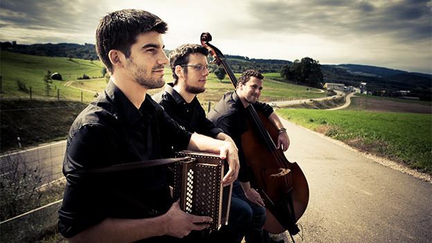 Drei junge Musiker mit Schwyzerörgeli und Kontrabass.