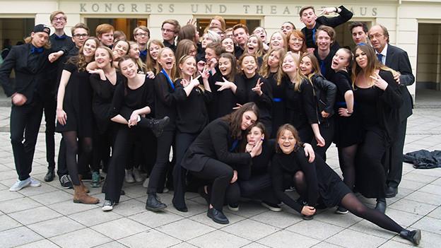 Eine Gruppe junger Menschen vor einem Kongresshaus.