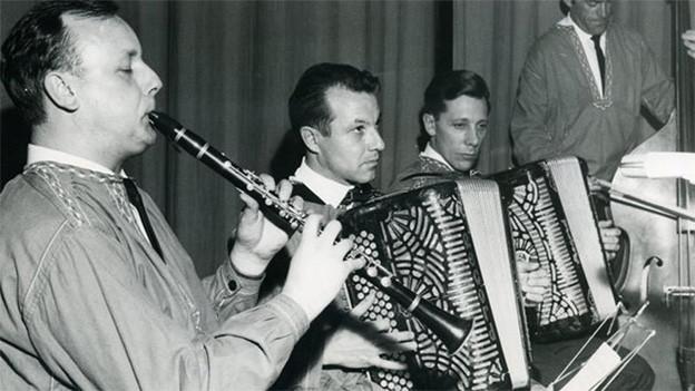 Schwarz-Weiss-Fotografie von einer Volksmusikformation in einer Gaststube.