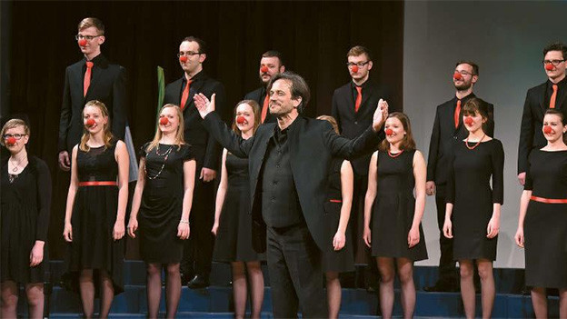 Ein Chor auf einer Bühne. Die Sängerinnen und Sänger tragen rote Clownnasen.