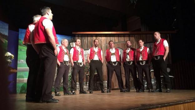 Der Jodlerklub Wattwil bei einem Auftritt, alle Mitglieder stehen in einem Halbkreis und singen.