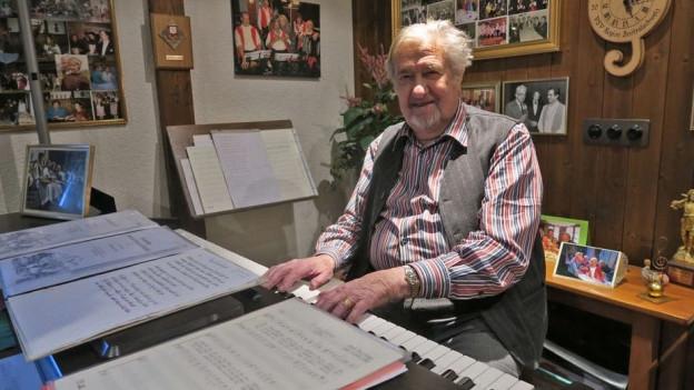 Hans Aregger sitzt am Klavier in seinem Musikzimmer.