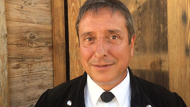 Ein Mann mit schwarzer Sennenjacke vor einer Holzwand.