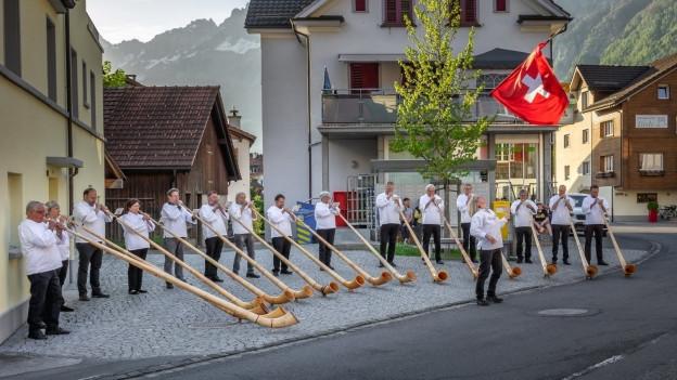 Alphornformation spielt auf Dorfplatz.