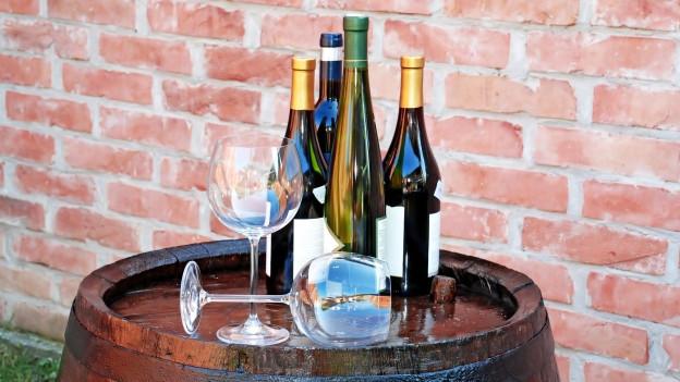 Mehrere Weinflaschen stehen auf dem Fass.