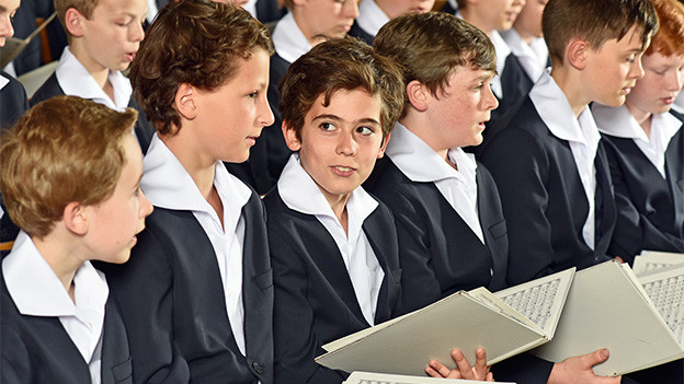 Junge Chorsänger mit Notenblättern.