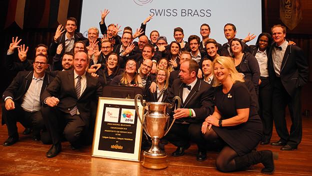 Eine Gruppe Musikanten vor einem Pokal.