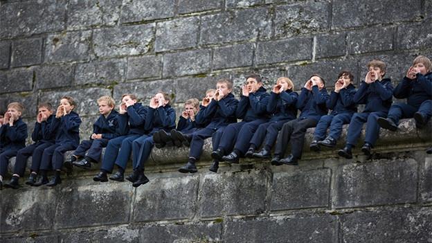 Junge Sänger sitzen nebeneinander auf einer hohen Mauer.